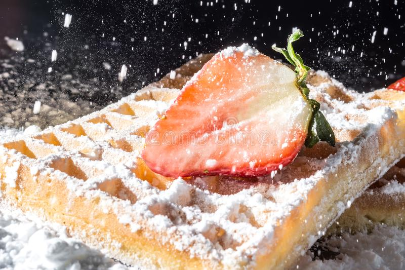 Il pane tostato dolce waffles con la fragola con le foglie sulla cima e sul vagliare la polvere di versamento dello zucchero nell fotografie stock libere da diritti
