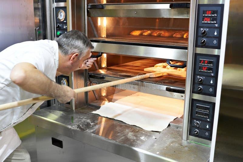 Il panettiere cuoce il pane in forno immagine stock