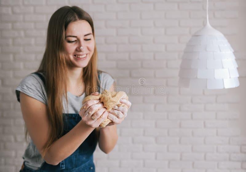 Il panettiere felice della donna impasta il grumo della pasta contro lo sfondo di un muro di mattoni e della lampada bianca fotografia stock