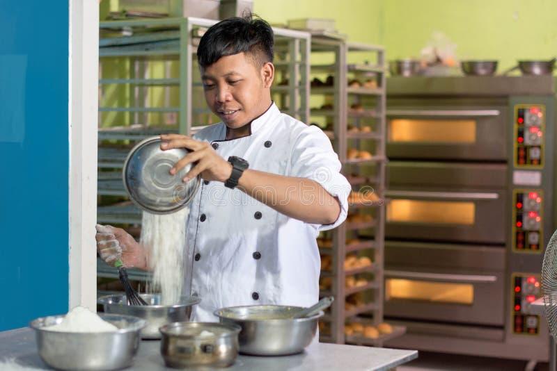 Il panettiere maschio asiatico, cuoco unico di pasticceria prepara la pasta con farina dentro la cucina del forno fotografia stock