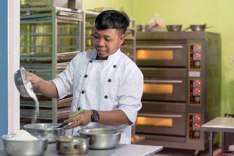 Il panettiere maschio asiatico, cuoco unico di pasticceria prepara la pasta con farina dentro la cucina del forno immagine stock