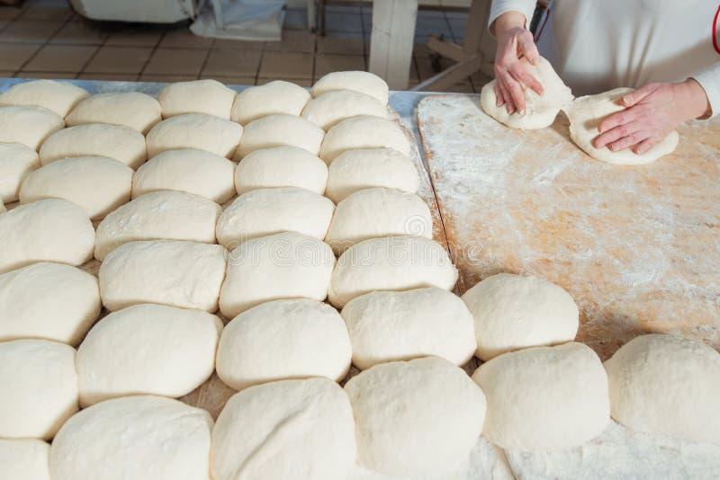 Il panettiere produce la pasta di pane fotografia stock libera da diritti