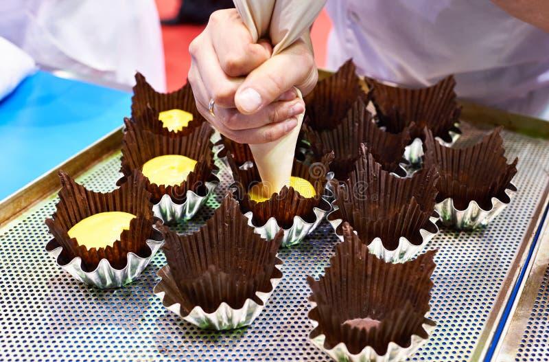 Il panettiere spinge la pasta nelle forme di carta del muffin immagine stock