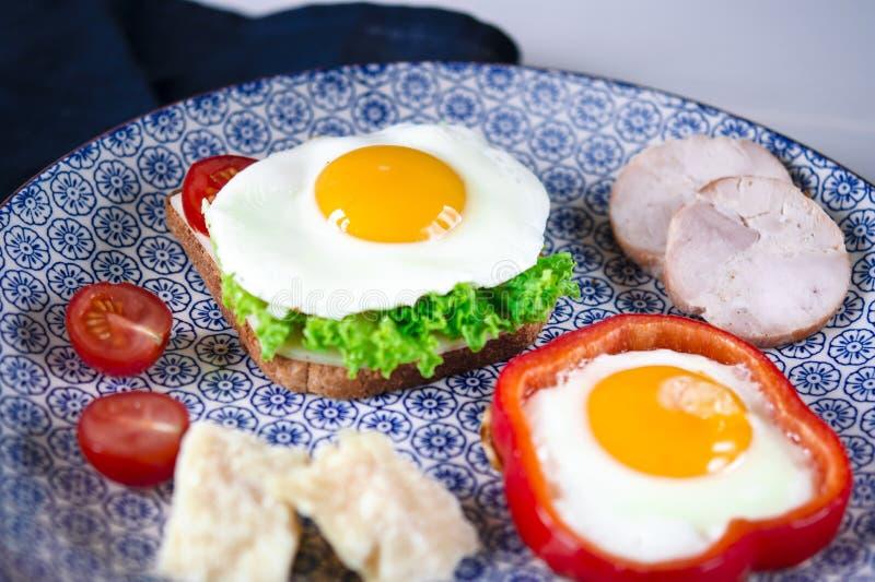Il panino con l'uovo, il prosciutto, il formaggio, il pane tostato e l'insalata lascia le bugie su un piatto con il pomodoro e l' fotografia stock
