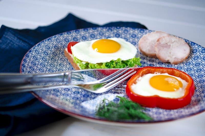 Il panino con l'uovo, il prosciutto, il formaggio, il pane tostato e l'insalata lascia le bugie su un piatto con il pomodoro e l' immagine stock