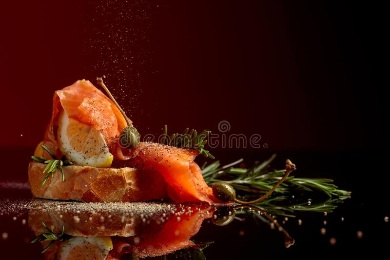 Il panino con il raccordo della trota, la fetta del limone, i capperi ed i rosmarini spruzzano con pepe immagine stock