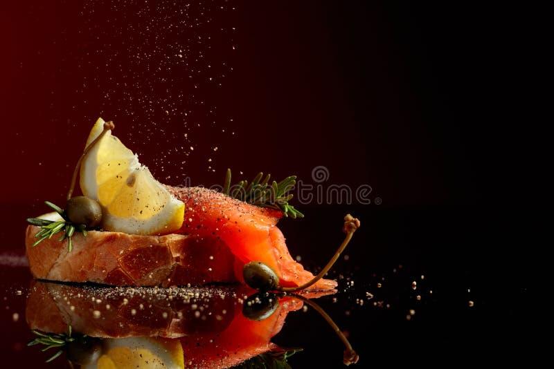 Il panino con il raccordo della trota, la fetta del limone, i capperi ed i rosmarini spruzzano con pepe fotografia stock libera da diritti