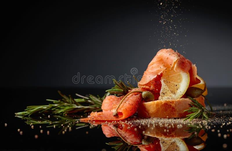 Il panino con il raccordo della trota, la fetta del limone, i capperi ed i rosmarini spruzzano con pepe immagini stock