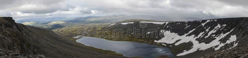 Il panorama del lago mountain in valle con i muschi e le rocce ha riguardato w fotografia stock
