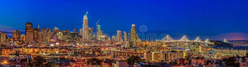Il panorama dell'orizzonte di San Francisco con la città si accende, il ponte della baia immagine stock libera da diritti
