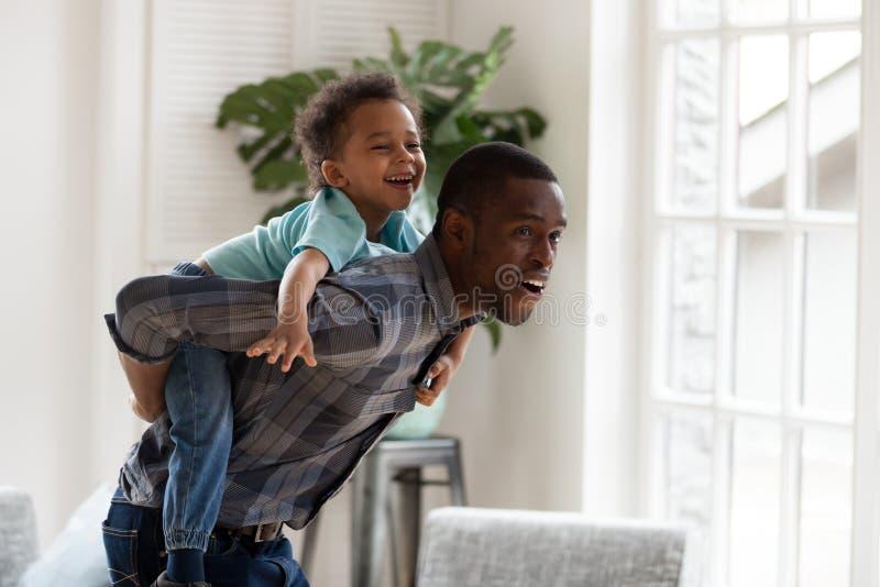 Il papà africano felice dà il piccolo giro di a due vie del figlio a casa fotografia stock libera da diritti