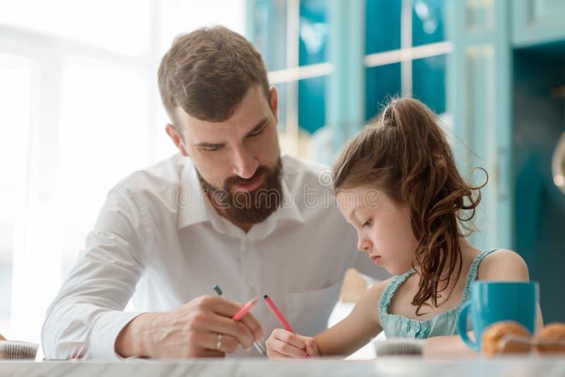 Il papà aiuta la figlia a disegnare fotografia stock libera da diritti