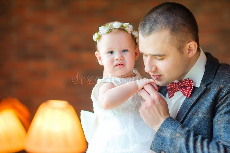 Il papà bacia delicatamente la mano della sua piccola figlia fotografia stock libera da diritti