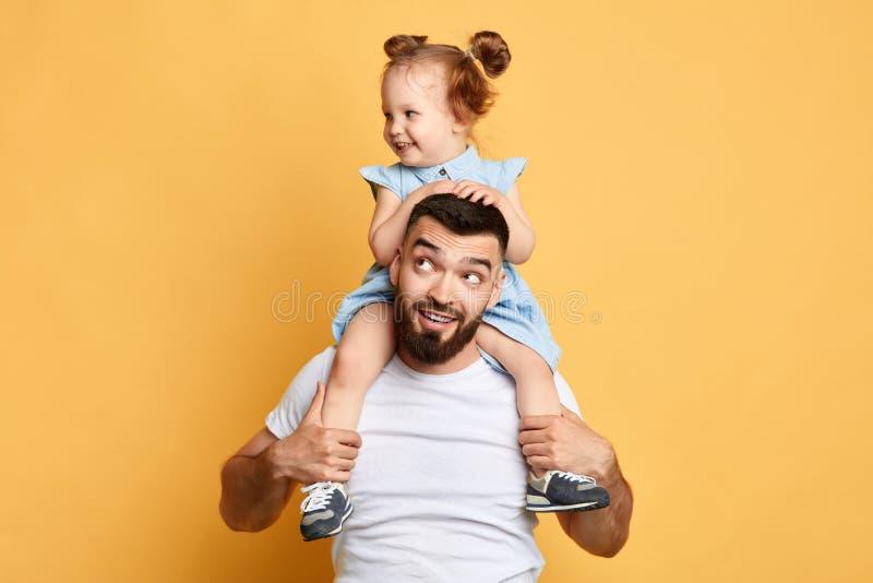 Il papà bello positivo porta il suo bambino sulle spalle fotografie stock