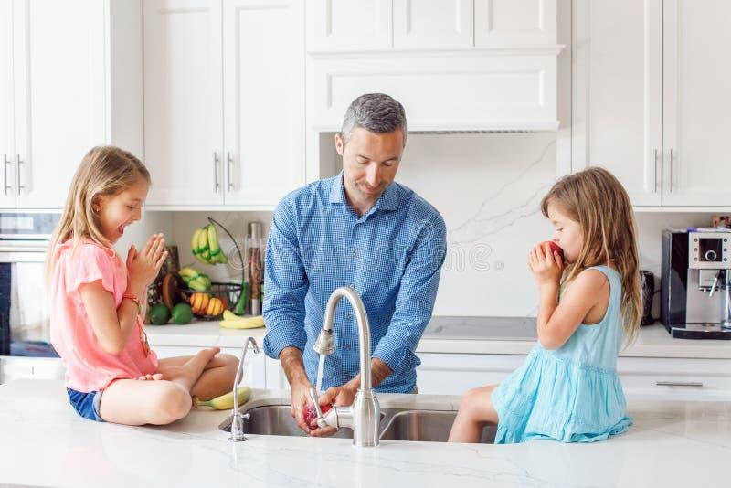 Il papà caucasico del padre dà a bambini le figlie frutta fresca per mangiare fotografie stock libere da diritti