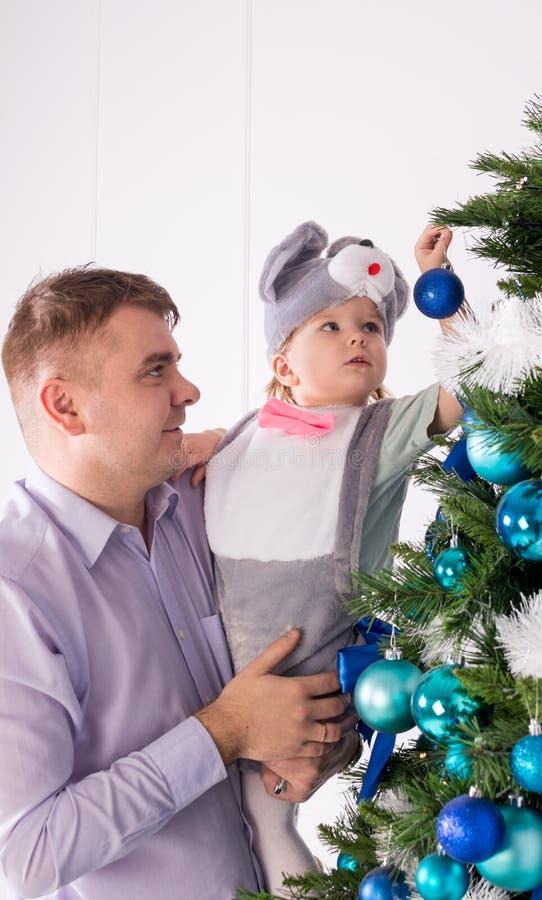 Il papà con la figlia decora un albero di Natale fotografia stock