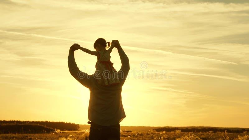 Il pap? continua le spalle del suo bambino caro, nei raggi del sole Il padre cammina con sua figlia sulle sue spalle nei raggi immagine stock libera da diritti