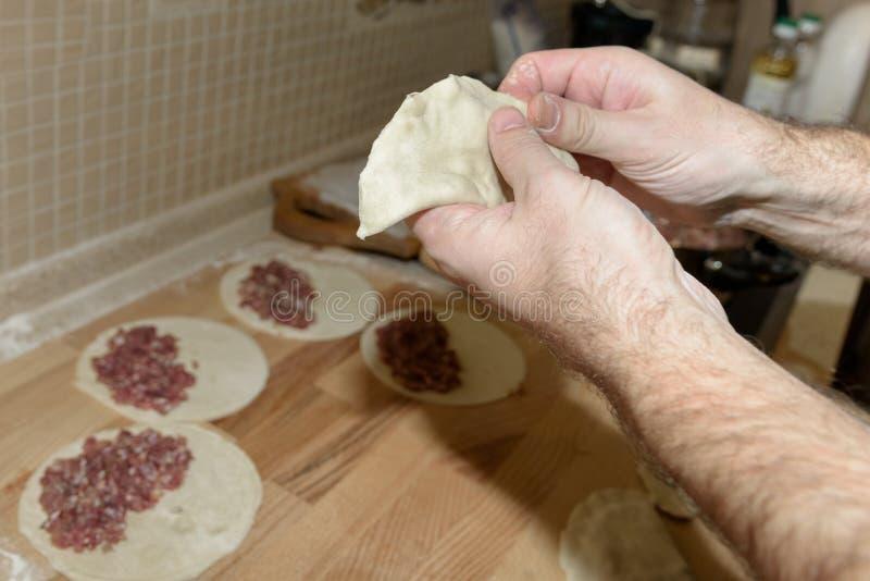Il papà cucina il chebureki Cuoco a casa Il singolo pezzo rotondo di pasta ha ripiegato il materiale da otturazione in una forma  fotografie stock libere da diritti