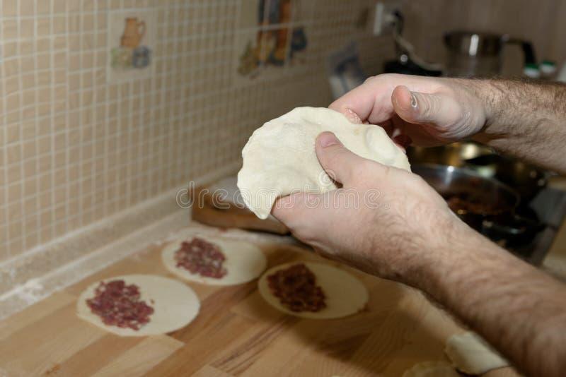 Il papà cucina il chebureki Cuoco a casa Il singolo pezzo rotondo di pasta ha ripiegato il materiale da otturazione in una forma  fotografia stock libera da diritti