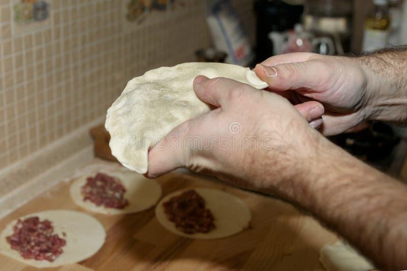 Il papà cucina il chebureki Cuoco a casa Il singolo pezzo rotondo di pasta ha ripiegato il materiale da otturazione in una forma  immagine stock libera da diritti