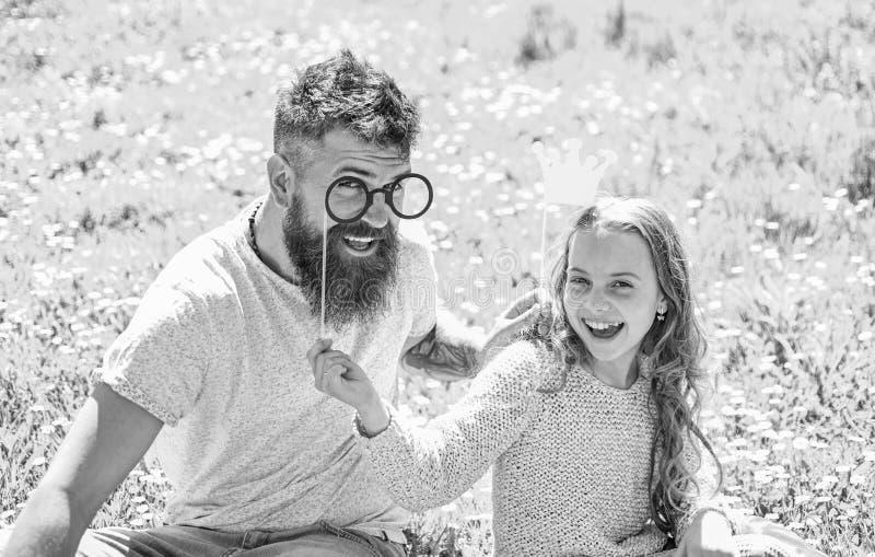 Il papà e la figlia si siede su erba a grassplot, fondo verde Concetto di principessa di Daddys Bambino e padre che posano con fotografia stock