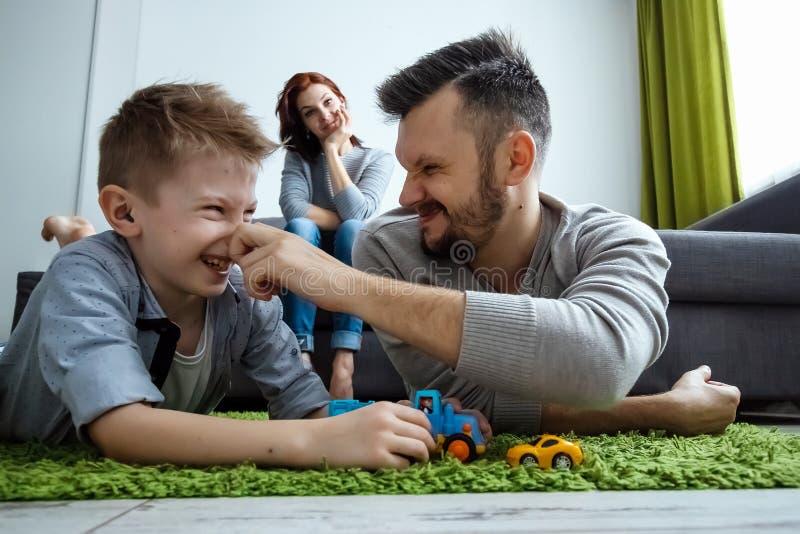 Il papà ed il figlio stanno giocando le automobili del giocattolo Il concetto di entusiasmo della famiglia, tempo con la famiglia fotografia stock