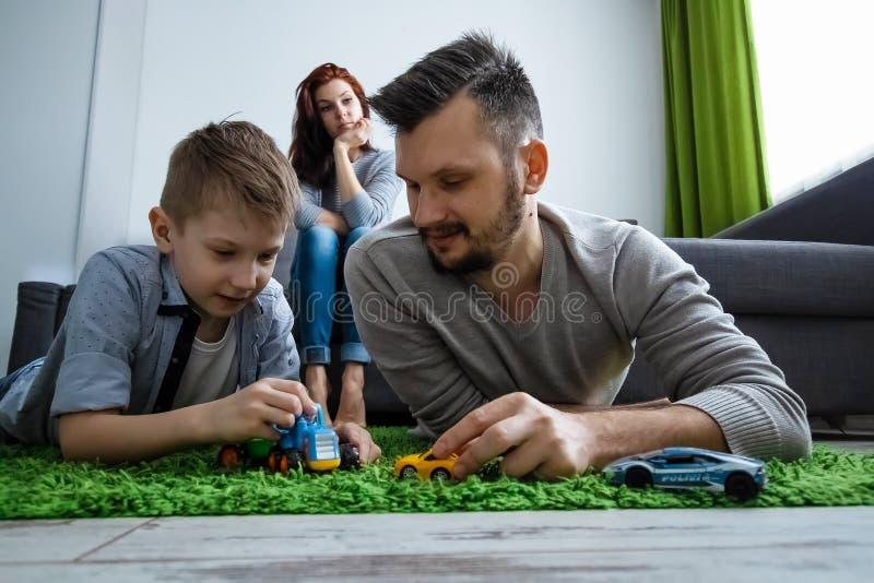 Il papà ed il figlio stanno giocando le automobili del giocattolo Il concetto di entusiasmo della famiglia, tempo con la famiglia immagini stock libere da diritti