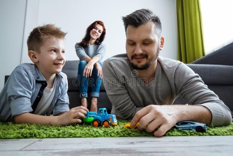Il papà ed il figlio stanno giocando le automobili del giocattolo Il concetto di entusiasmo della famiglia, tempo con la famiglia fotografie stock libere da diritti