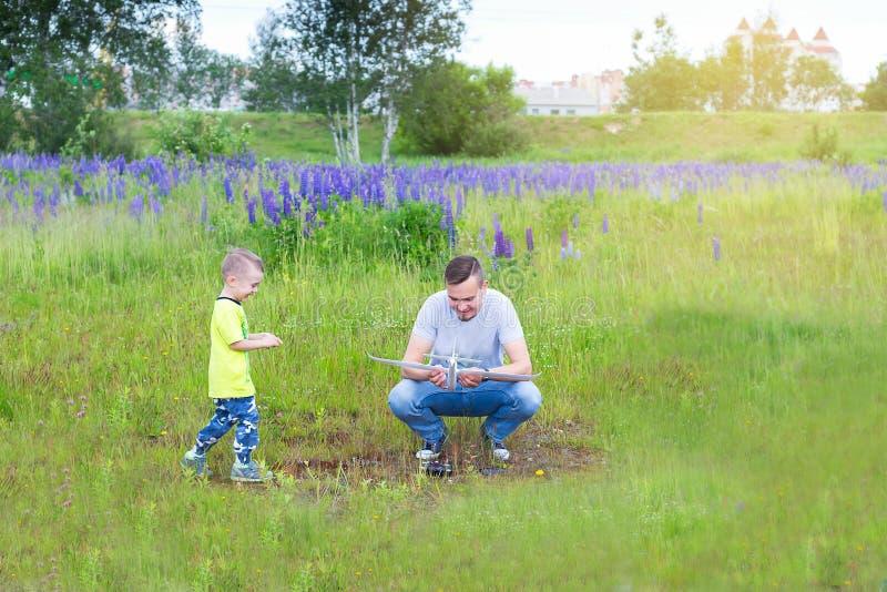 Il papà ed il figlio lanciano un aereo sul telecomando radio fotografia stock libera da diritti