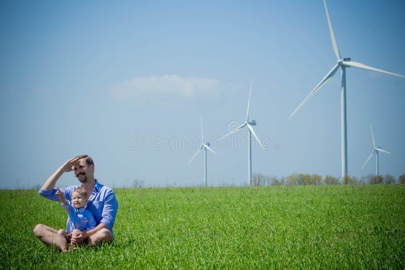 Il papà ed il figlio stanno esaminando i generatori eolici fotografia stock libera da diritti