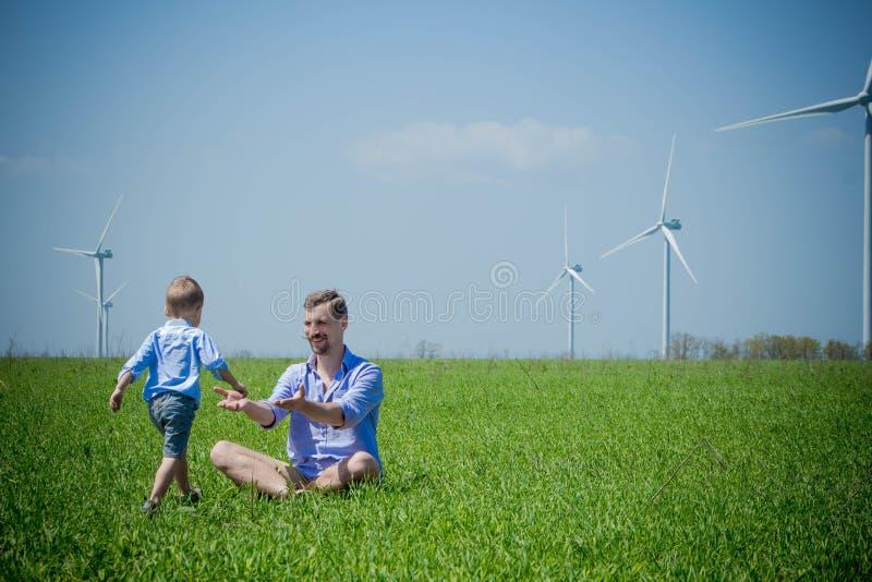 Il papà ed il figlio stanno giocando vicino ai generatori eolici immagini stock libere da diritti