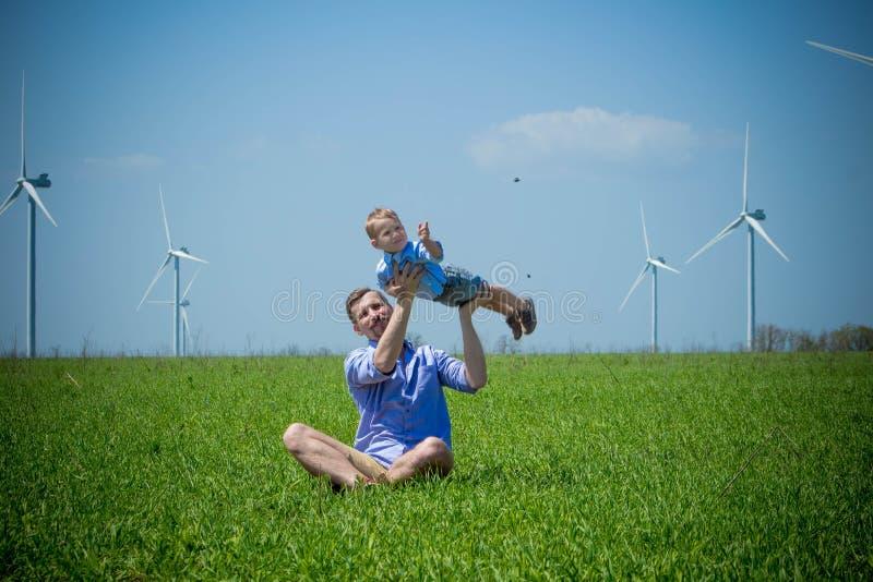 Il papà ha alzato suo figlio ed ha circondato vicino ai generatori eolici fotografia stock