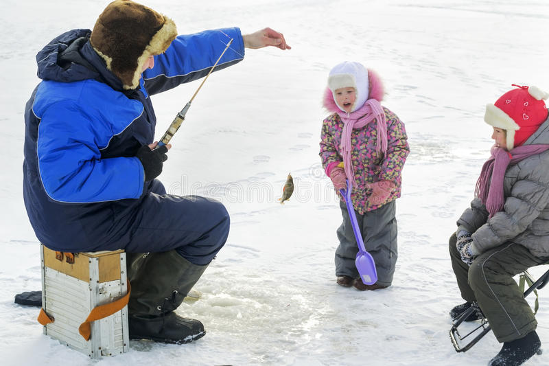Il papà passa il suo tempo libero sulla pesca dell'inverno fotografia stock