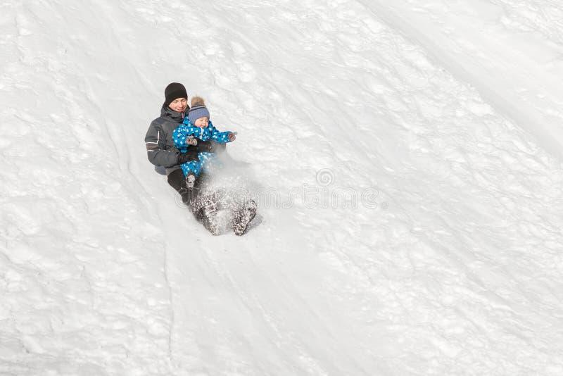 Il papà preoccupantesi rotola giù una collina della neve con mio figlio nel giorno gelido dell'inverno fotografia stock libera da diritti
