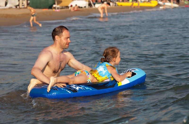 Il papà tiene il bambino che guida un'onda fotografia stock libera da diritti