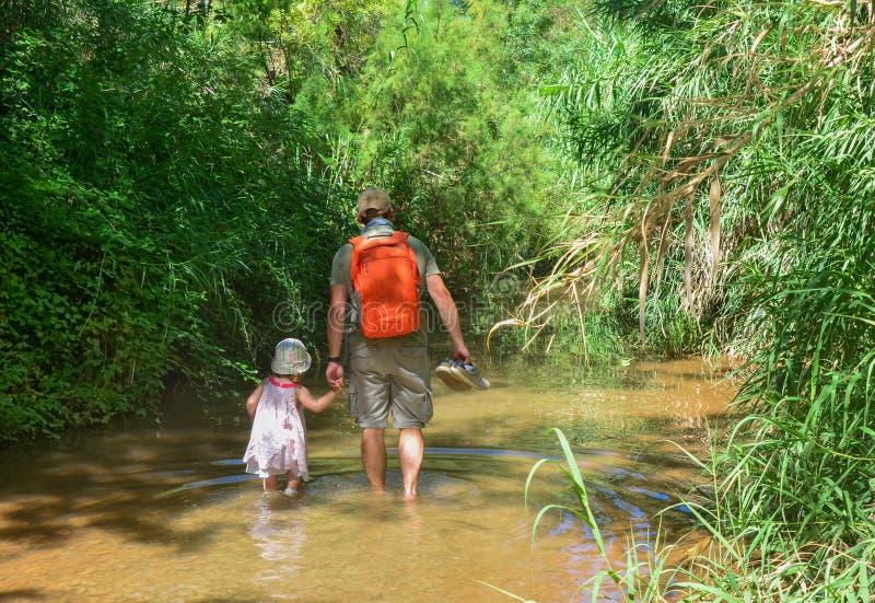 Il papà tiene sua figlia dalla mano e dalla passeggiata lungo il fiume fotografia stock
