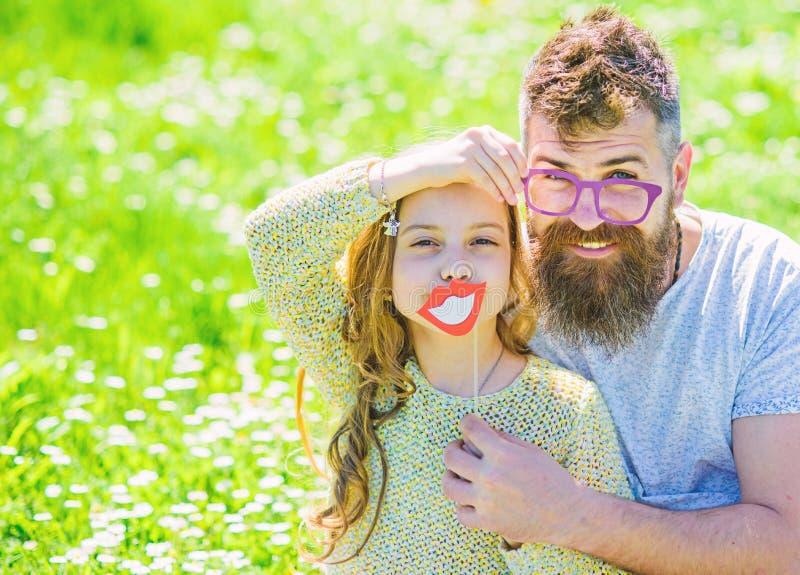 Il pap? e la figlia si siede su erba a grassplot, fondo verde Concetto di paternit? La famiglia spende lo svago all'aperto Bambin immagine stock