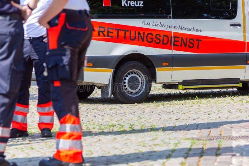 Il paramedico femminile tedesco sta davanti ad un'automobile dell'ambulanza fotografie stock libere da diritti