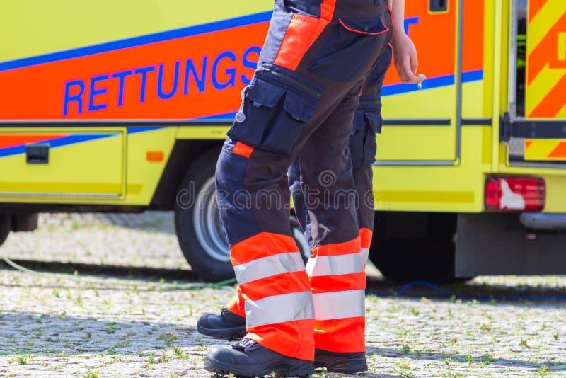 Il paramedico femminile tedesco sta davanti ad un'automobile dell'ambulanza fotografia stock