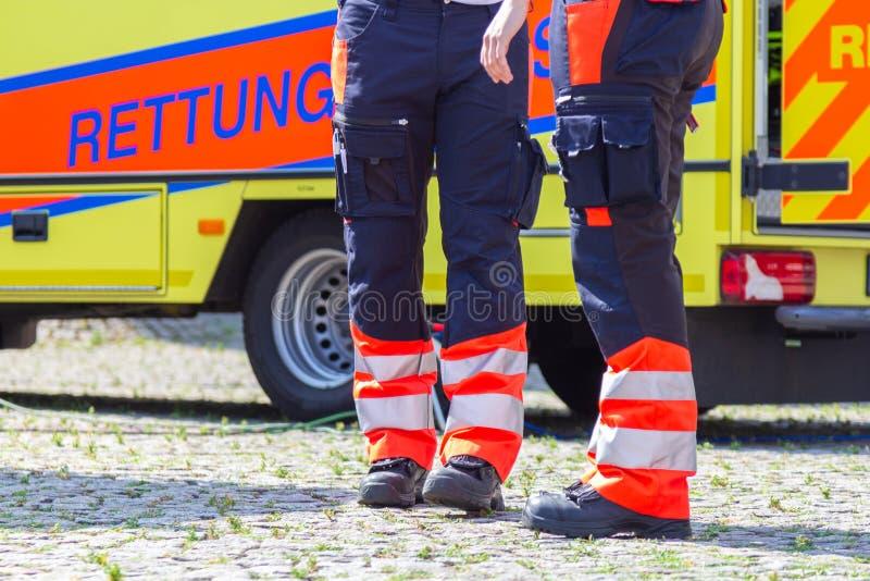 Il paramedico femminile tedesco sta davanti ad un'automobile dell'ambulanza fotografie stock