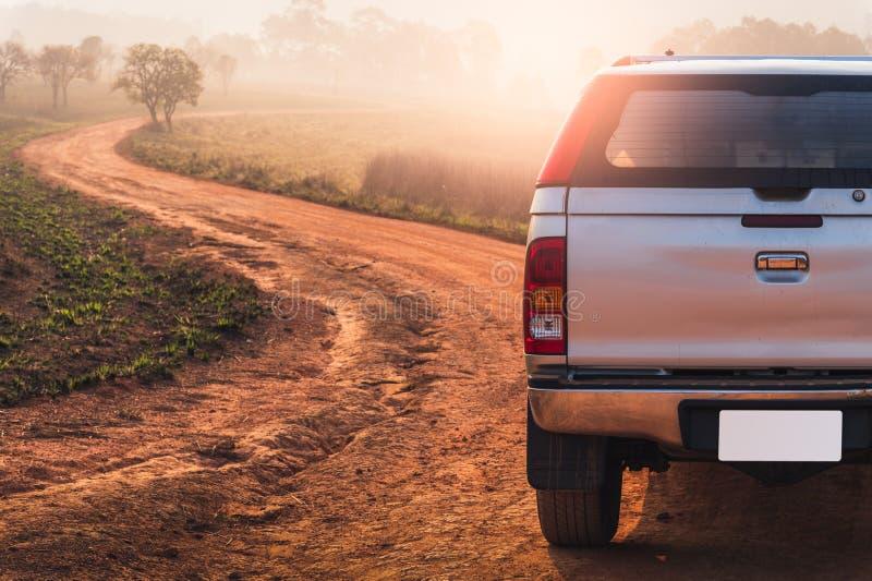 Il parcheggio di veicolo 4x4 accanto della pista fuori strada nel campo della savanna il concetto dell'avventura, del viaggio, di immagine stock libera da diritti