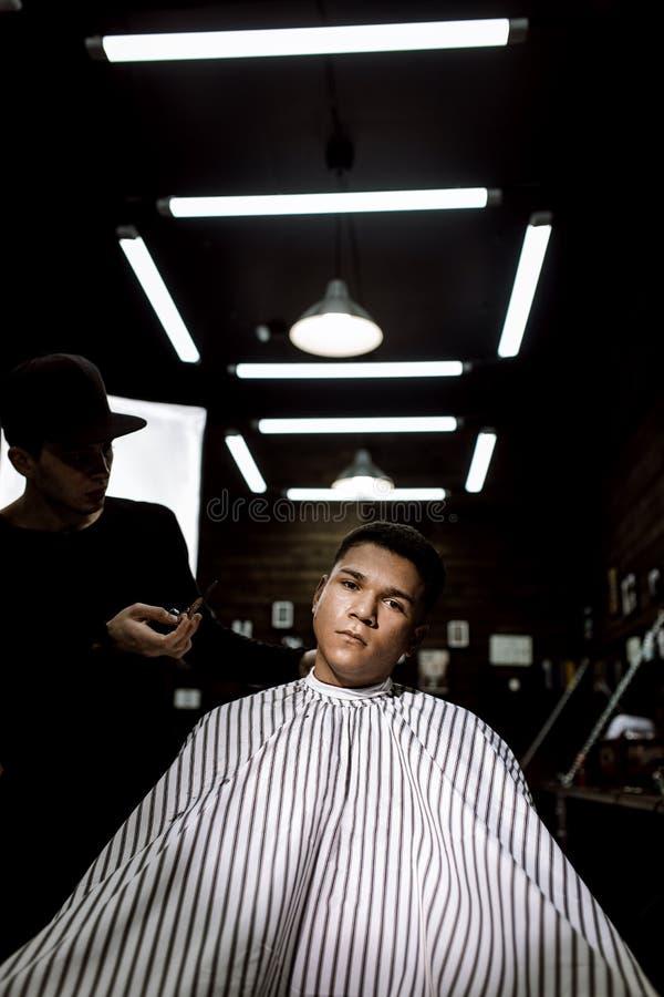 Il parrucchiere alla moda Il barbiere di modo fa un'acconciatura alla moda per un uomo moro che si siede nella poltrona fotografia stock libera da diritti