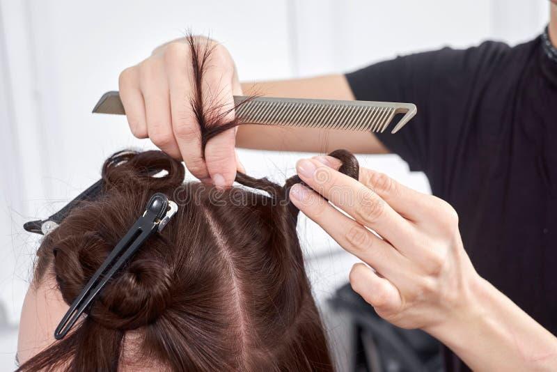 Il parrucchiere del primo piano fa l'acconciatura per la giovane donna nel salone di bellezza immagini stock