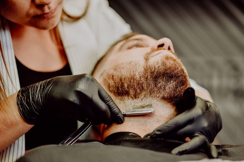 Il parrucchiere della ragazza rade la sua barba con un rasoio dell'uomo immagini stock