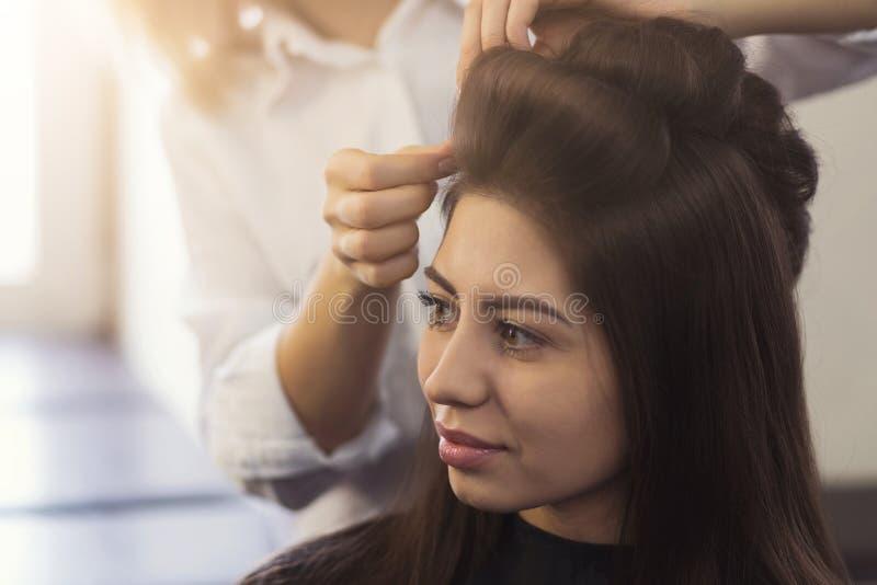 Il parrucchiere fa i riccioli sui capelli marroni del ` s del cliente fotografia stock