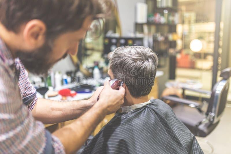 Il parrucchiere fa l'acconciatura con la tosatrice al parrucchiere fotografia stock
