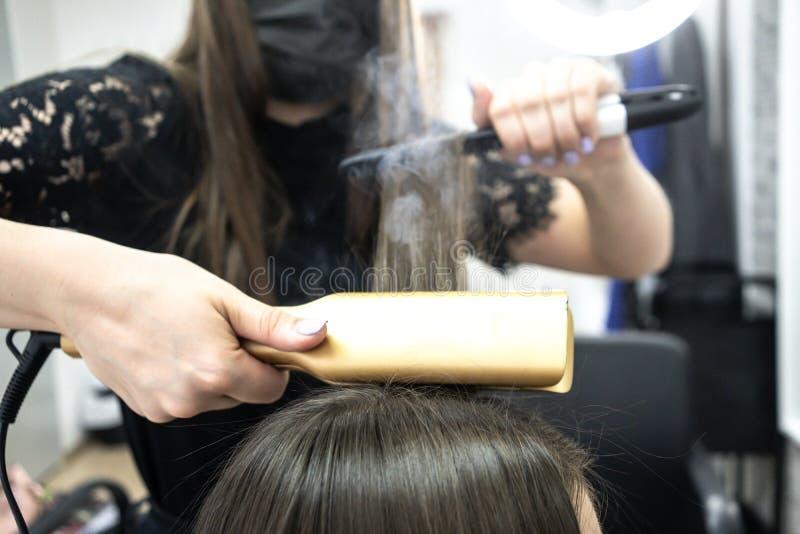 Il parrucchiere fa la laminazione dei capelli in un salone di bellezza per una ragazza con capelli castana fotografia stock
