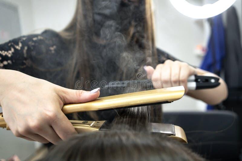 Il parrucchiere fa la laminazione dei capelli in un salone di bellezza per una ragazza con capelli castana fotografie stock