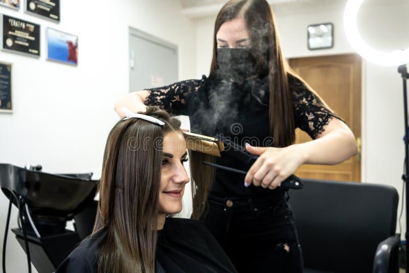 Il parrucchiere fa la laminazione dei capelli in un salone di bellezza per una ragazza con capelli castana fotografia stock libera da diritti