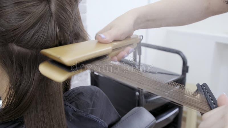 Il parrucchiere fa la laminazione dei capelli in un salone di bellezza per una ragazza con capelli castana immagini stock